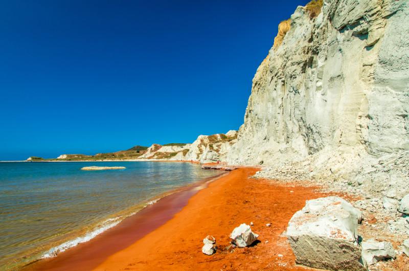 Una playa de Grecia de arena roja junto a acantilados ...